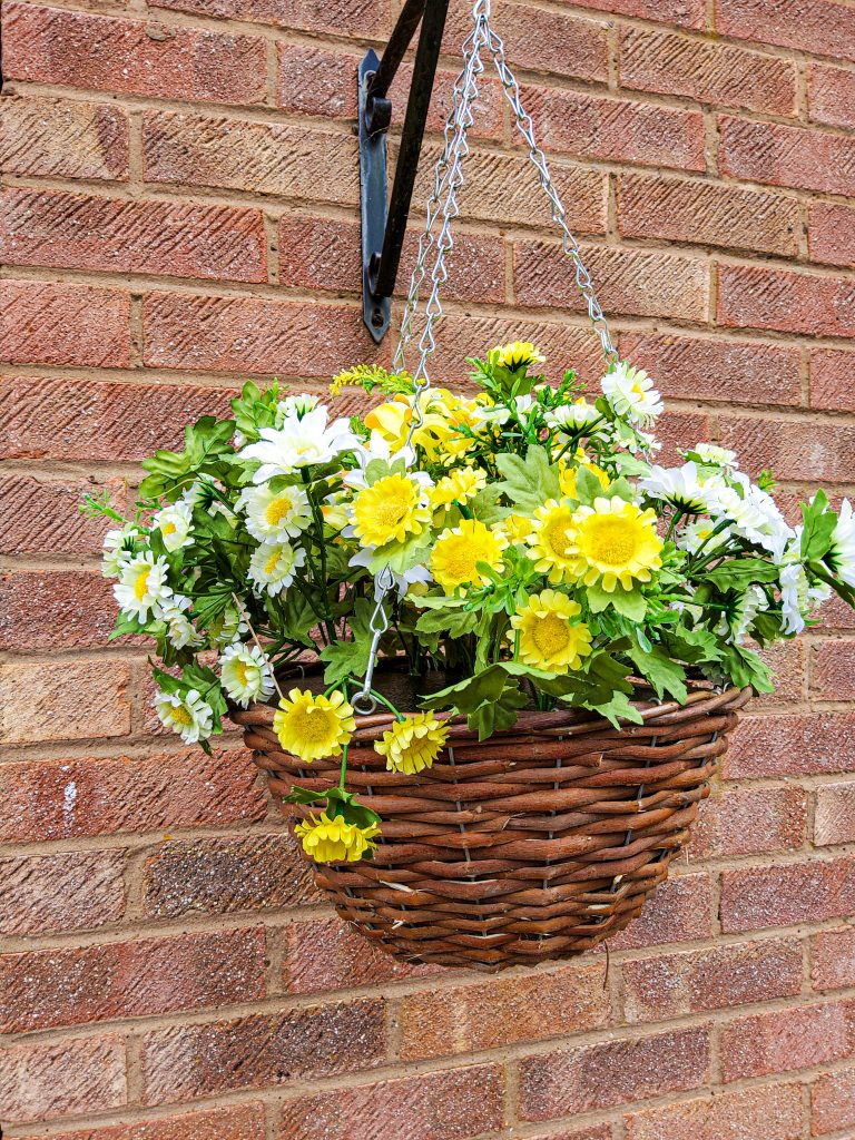 Budget friendly home decor. Faux Hanging basket. Yellow and white daisies with green leaves hanging from a hook against a brick wall.